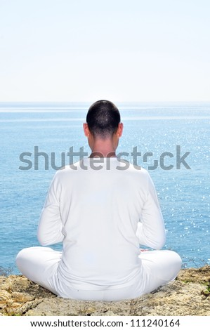 someone dressed in white meditating on the beach