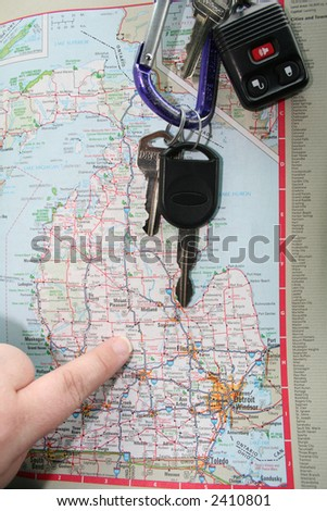 Someone following a road map with their finger with car keys. - stock photo