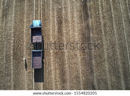 someone have a lot of work at the field. Truck in the field. Aerial shot of an agricultural wheat field, a combine harvester and a truck in Europe. Aerial View Of Rural Landscape. Harvesting Of Wheat  ストックフォト ©