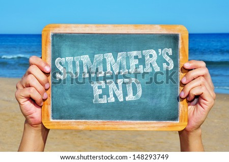 someone holding a blackboard with the sentence summers end written in it on the beach