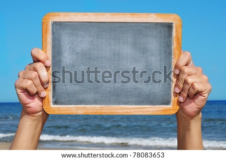 someone holding a blank blackboard at the beach