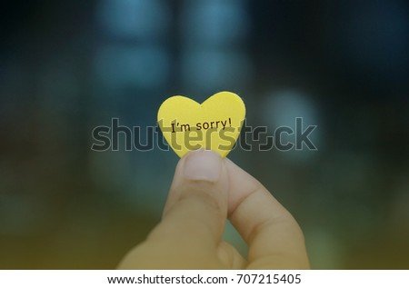 Someone holding a yellow heart-shaped with the sentence I'm Sorry! written on it with a retro effect. Love concept #707215405