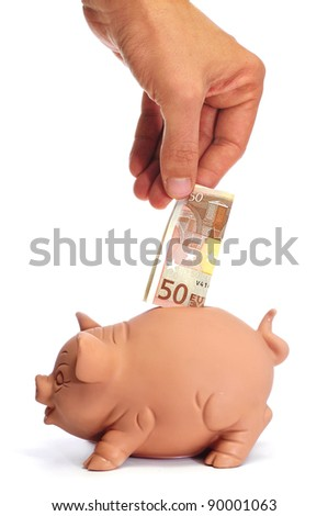 someone inserting a ticket 50 euros in a piggy bank - stock photo