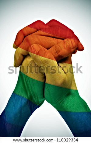 someone joining his hands, painted as the rainbow flag, symbolizing union