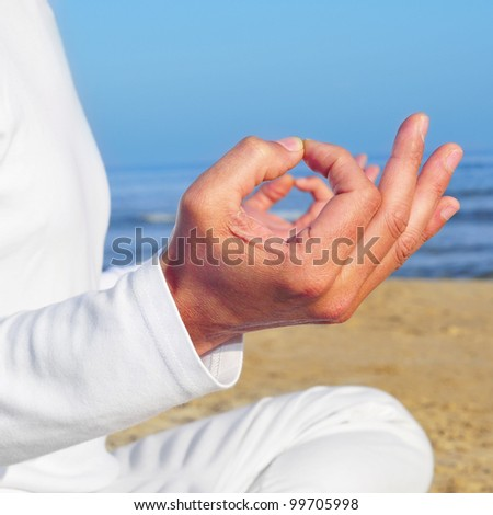 someone meditating on the beach