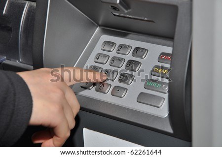 Someone pressing number button on ATM machine - stock photo