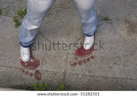 Someone's legs on drawn red footsteps on old concrete floor
