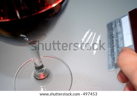 Someone using a platinum card to cut up cocaine. in muted cold tones