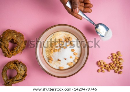 someone using a spoon to add sugar to a plate of garri, with groundnuts and fish