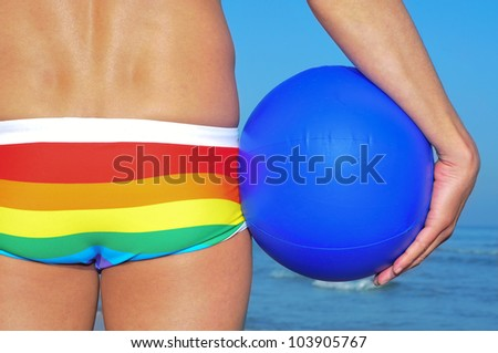someone wearing a rainbow swimsuit on the beach holding a beach ball
