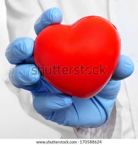someone wearing a white coat and blue medical gloves showing a red heart