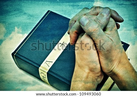 someone with hands clapsed praying on a bible