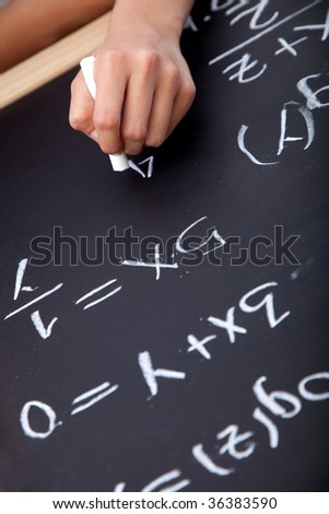 Someone writing maths equations on a chalkboard