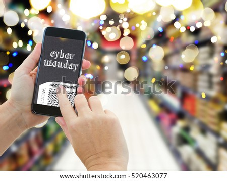 someones hands holding mobile smart phone with mobile shop on supermarket blur background and shopping bags - cyber monday e-commerce concept