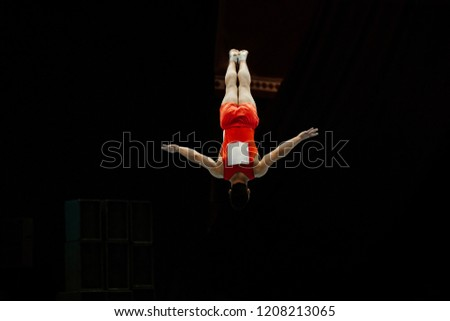 somersault gymnast athlete on floor exercise in black background #1208213065