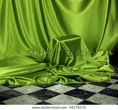 Something secret veiled under green satin silky cloth fabric