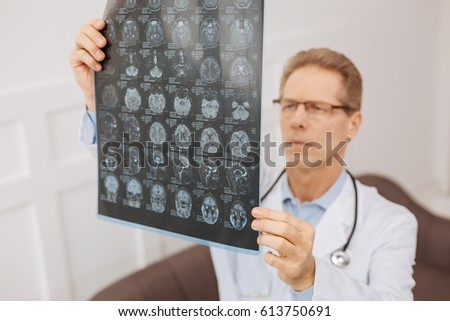 Something wrong about it. Clever distinguished successful surgeon examining brain scans of his patient and being unsure about his diagnosis