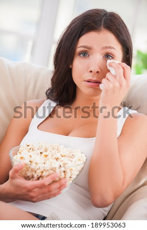 Sometimes I am so sentimental. Beautiful young woman holding handkerchief and crying while watching movie