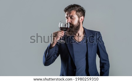 Sommelier, degustator with glass of wine, winery, male winemaker. Man holding glass of champagne in hand. Man with a glass of red wine in his hands. Beard man, bearded, sommelier tasting red wine. Foto stock ©