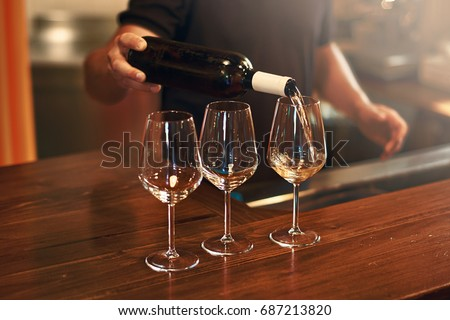 Sommelier fills the glasses during pinot gris wine tasting
