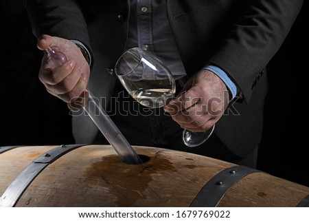 Sommelier makes a selection of red wine from an oak barrel. ecological wine production on the farm. Foto stock ©