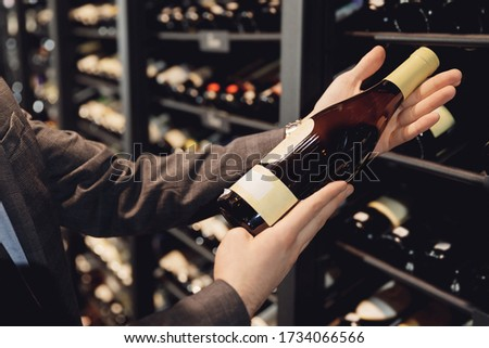 Sommelier man with wine bottle near rack store restaurant with exquisite drinks. Stock photo ©