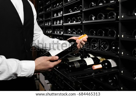 Sommelier with wine bottle near rack at store #684465313
