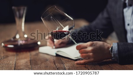 Sommeliers male hold glass red wine tasting degustation card. Stock photo ©