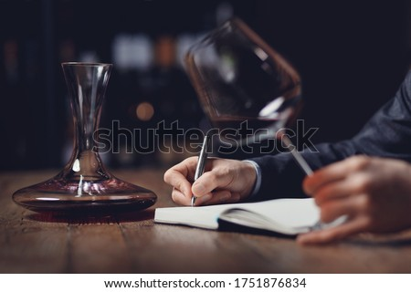 Sommeliers male tasting red wine and making notes aroma degustation card. Stock photo ©