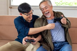 Son and dad fight for gamepad in cozy home, smiling and laughing together. Senior Asian man challenge with Young Asian man gamer. Father's day and happy family concept.