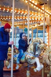 son and dad ride a carousel in winter in Moscow 2020 for Christmas