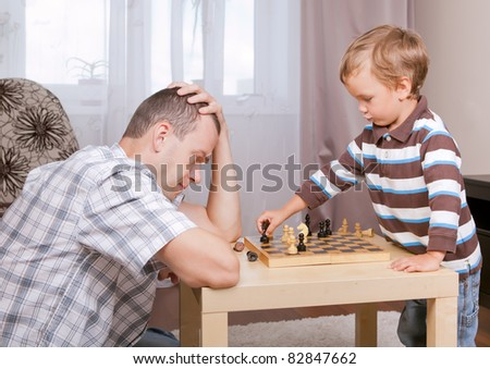 Son and father playing chess in room