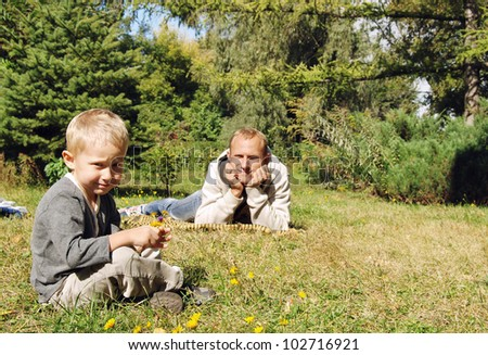 Son and father relax on the green lawn at the park - stock photo