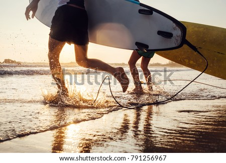 Shutterstock Son and father surfers run in ocean waves with long boards. Close up splashes and legs image