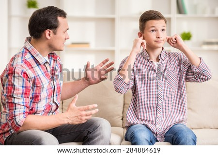 Son closing ears while father scolding  him. ストックフォト ©