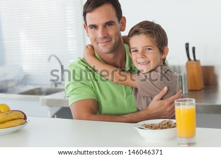 Son embracing his father while having breakfast in the kitchen
