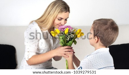 Son gives his beloved mother a beautiful bouquet of tulips.The concept of the celebration,woman's day.