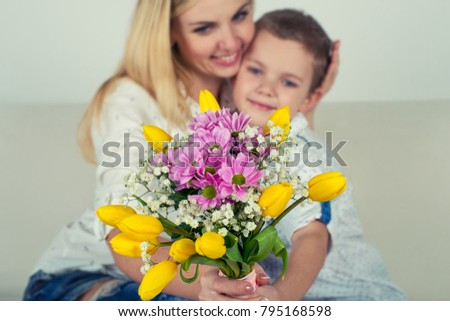 Son gives his beloved mother a beautiful bouquet of tulips.The concept of the celebration,women's day.	 #795168598
