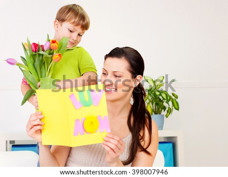 Son giving a bouquet of tulips to his mother. #398007946