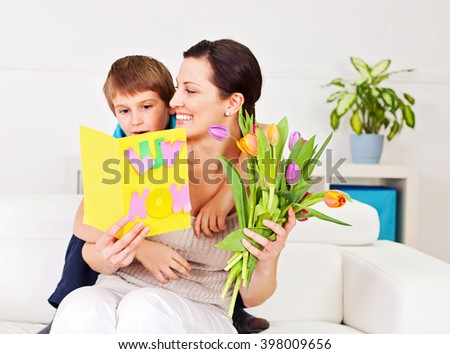 Son giving a bouquet of tulips to his mother. #398009656