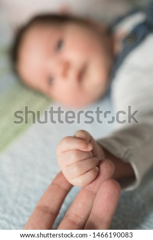 Son holds father by the hand. close-up. Closeup of a senior man and girl holding hands