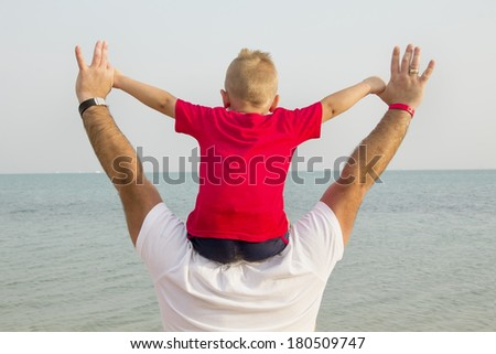 son in a red shirt sitting on his father\'s shoulders and looks at the sea