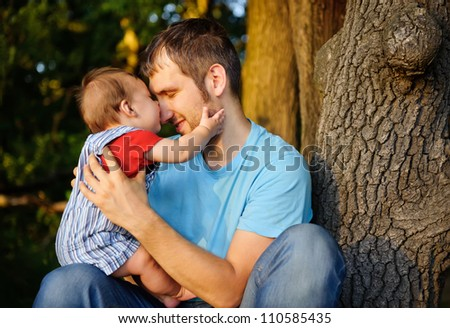 Son kissing his father. Outdoor