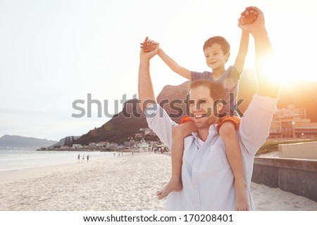 Son on fathers shoulders at the beach having fun at sunset together