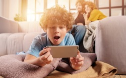 Son plays online with smartphone. Concept of addiction, dependency, problem