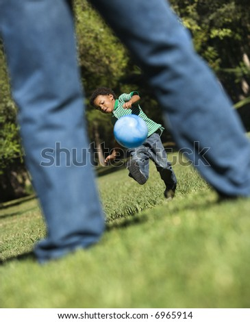 Son running and kicking ball towards father in park.