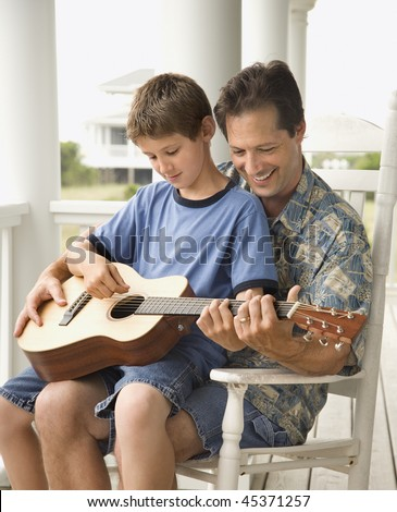 Son sits on his father's lap while playing guitar. Vertical shot.