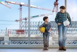 Son stood with gesture imitating his father, with a building being built and a crane in the background, child boy grow up wanting to be an engineer like his father