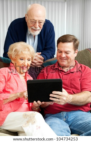Son teaching his elderly parents how to use a new tablet PC.