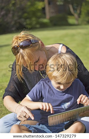 Son using touchscreen tablet PC with his mother. Outdoor, in the garden.